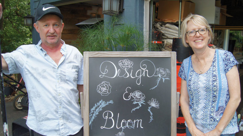 Cleaning up the floral prep aftermath, ProAct Adult Day Services participant Craig Blake, left, lightens the load for Design n Bloom owner Gayle Kenow.