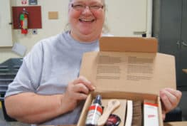 ProAct's Linda Gorenson works in assembly and quality control, handling boxes, labels, products and inserts for Red Wing Shoe branded care kits.