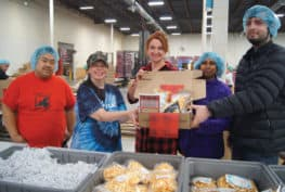 ProAct participants and staff package multiple gift box varieties for a growing effort that blends local culture with high quality Minnesota products. At center is Katie Sterns, CEO of Share Local Love.
